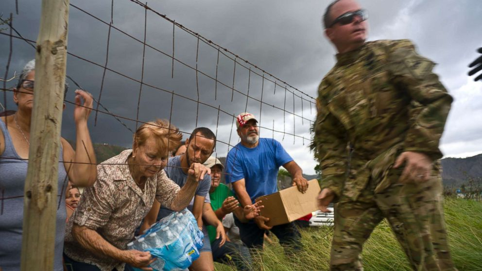 A member of the Puerto Rican National Guard delivers food and water brought via helicopter to victims of Hurricane Maria, in the San Lorenzo neighborhood of Morovis, Puerto Rico, Oct. 7, 2017.
