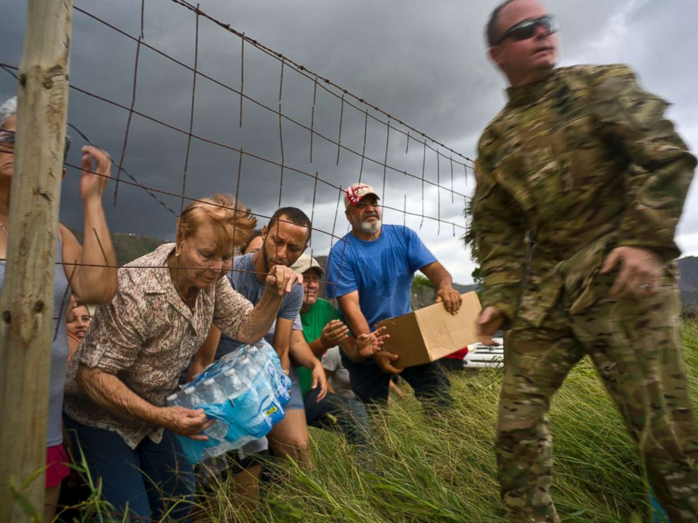 PHOTO: A member of the Puerto Rican National Guard delivers food and water brought via helicopter to victims of Hurricane Maria, in the San Lorenzo neighborhood of Morovis, Puerto Rico, Oct. 7, 2017.