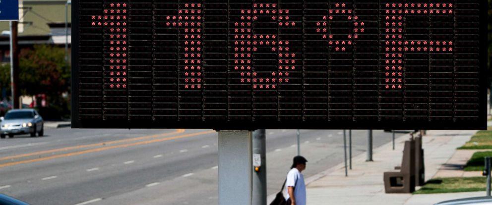 PHOTO: The temperature reads 116 degrees Fahrenheit as a pedestrian walks in Canoga Park, Calif., Aug. 7, 2012.