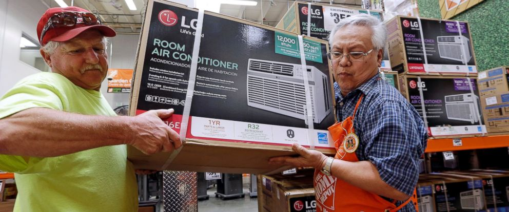 In this file photo, store greeter Danny Olivar, right, lends a hand to a customer to heft an air conditioning unit from a rapidly declining stock at a Home Depot store.