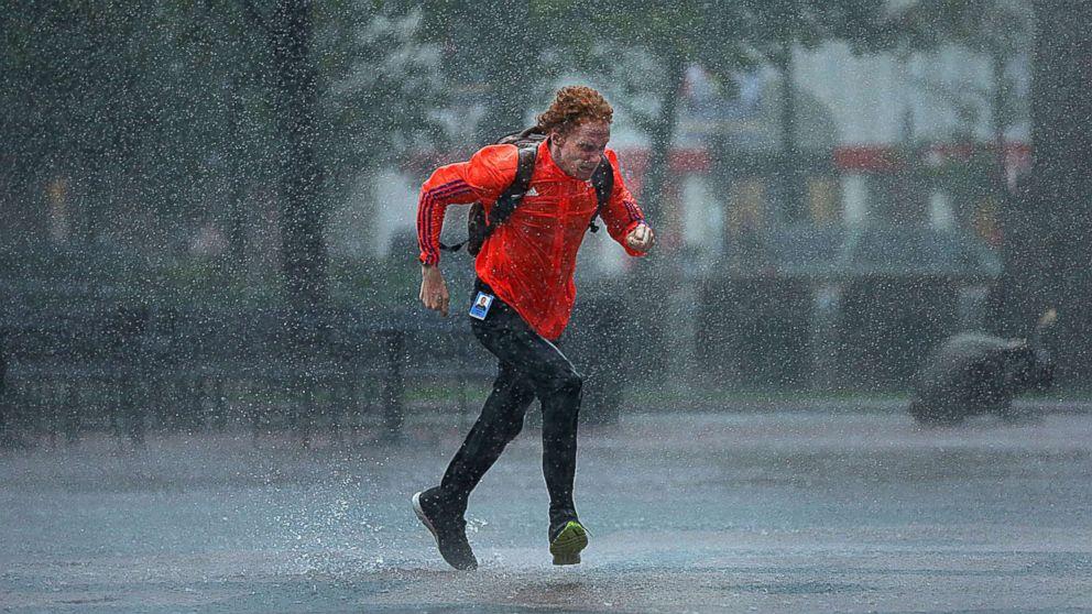 A pedestrian runs through heavy rain in Boston's Copley Square on Sep. 18, 2018.