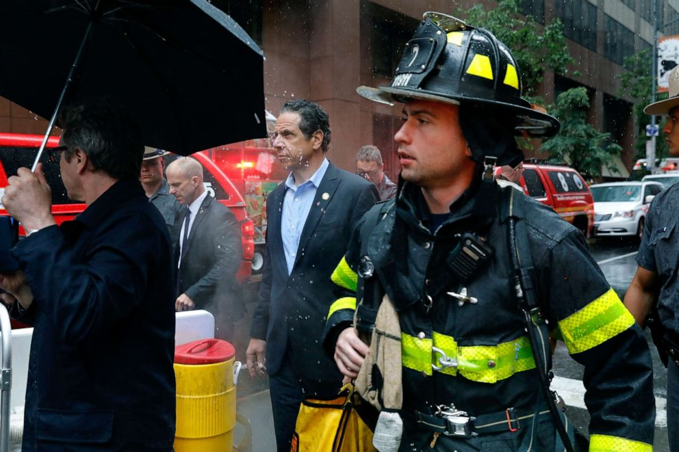 PHOTO: New York Gov. Andrew Cuomo, center, and first responder personnel walk near the scene where a helicopter was reported to have crash landed on top of a building in midtown, June 10, 2019, in New York.