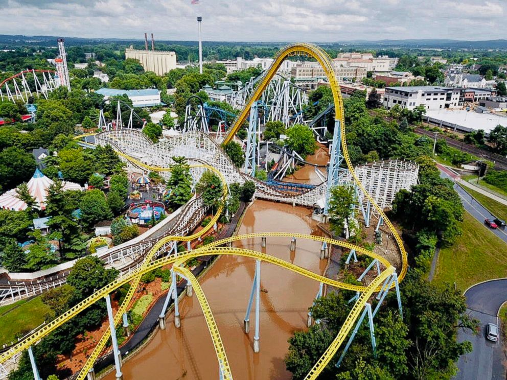 PHOTO: In this July 23, 2018, aerial image provided by The Wyse Choice photography in Hershey, Penn., muddy brown floodwaters in Spring Creek flow beneath the Skyrush roller coaster and the Comet roller coaster at the Hersheypark theme park.