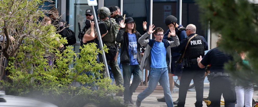 PHOTO: Students and teachers raise their hands as the exit the scene of a shooting at the STEM School Highlands Ranch, May 7, 2019, in Highlands Ranch, Colo.