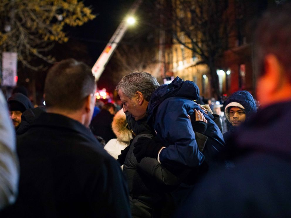 New York City Mayor Bill de Blasio hugs a resident of the apartment building where 12 people died in the Bronx on Dec. 28, 2017.
