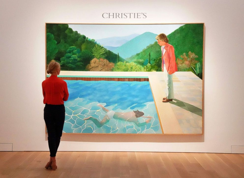 """A woman looks at David Hockneys """"Portrait of an Artist (Pool with Two Figures)"""" during a press preview at Christie's New York, Sept. 13, 2018."""
