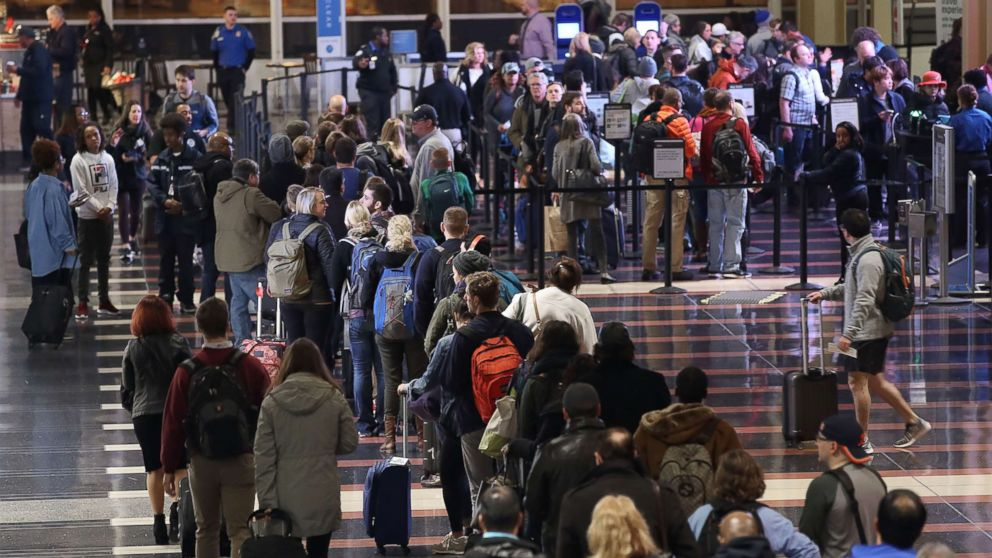 Travelers wait in line to go through the security area at Reagan National Airport on Nov. 21, 2017 in Arlington, Va.