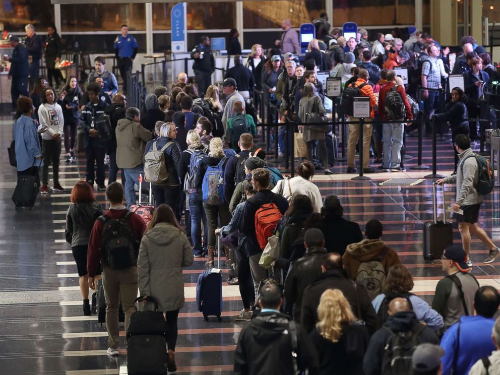 PHOTO: Travelers wait in line to go through the security area at Reagan National Airport on Nov. 21, 2017 in Arlington, Va.