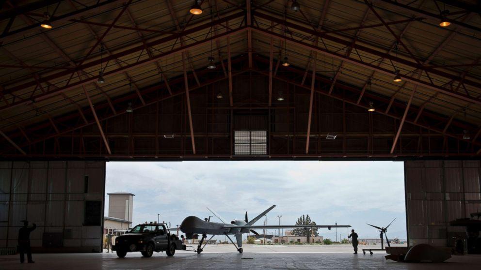 A group of Airmen tow an aircraft into a hangar, April 25, 2013 at Holloman Air Force Base, New Mexico.