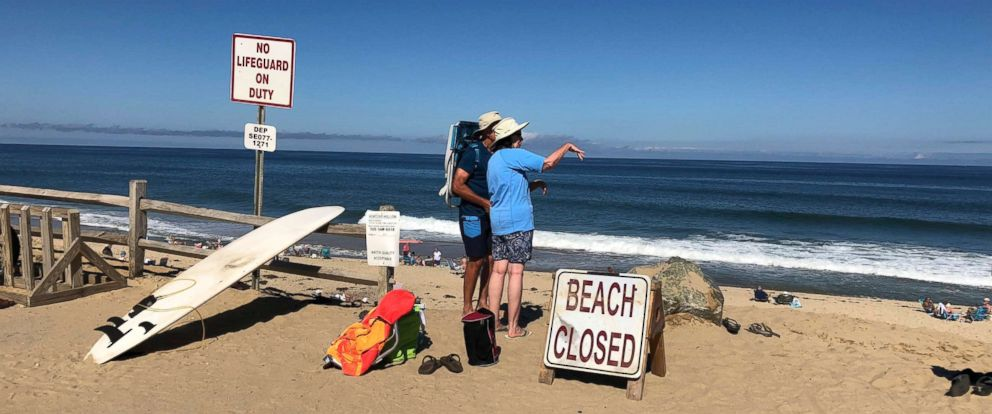 PHOTO: Two people look out at the shore after a reported shark attack at Newcomb Hollow Beach in Wellfleet, Mass., Sept. 15, 2018.