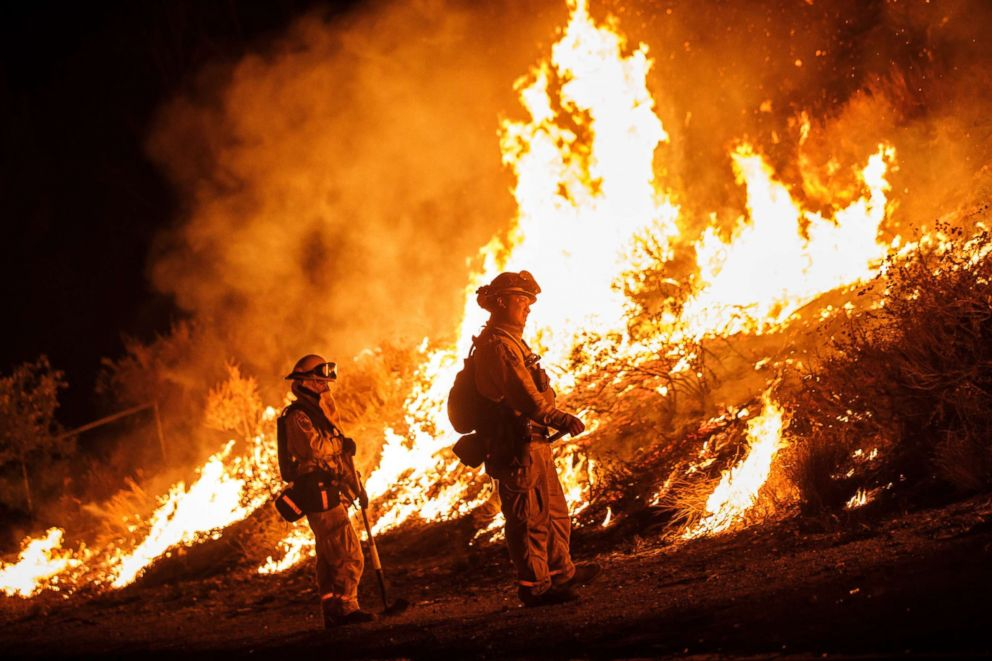 PHOTO: Firefighters conduct a burn operation to remove fuel around homes on Grand Ave as the Holy Fire grows to more than 10,000 acres as the wildfire comes closer to Lake Elsinore, Aug. 10, 2018.