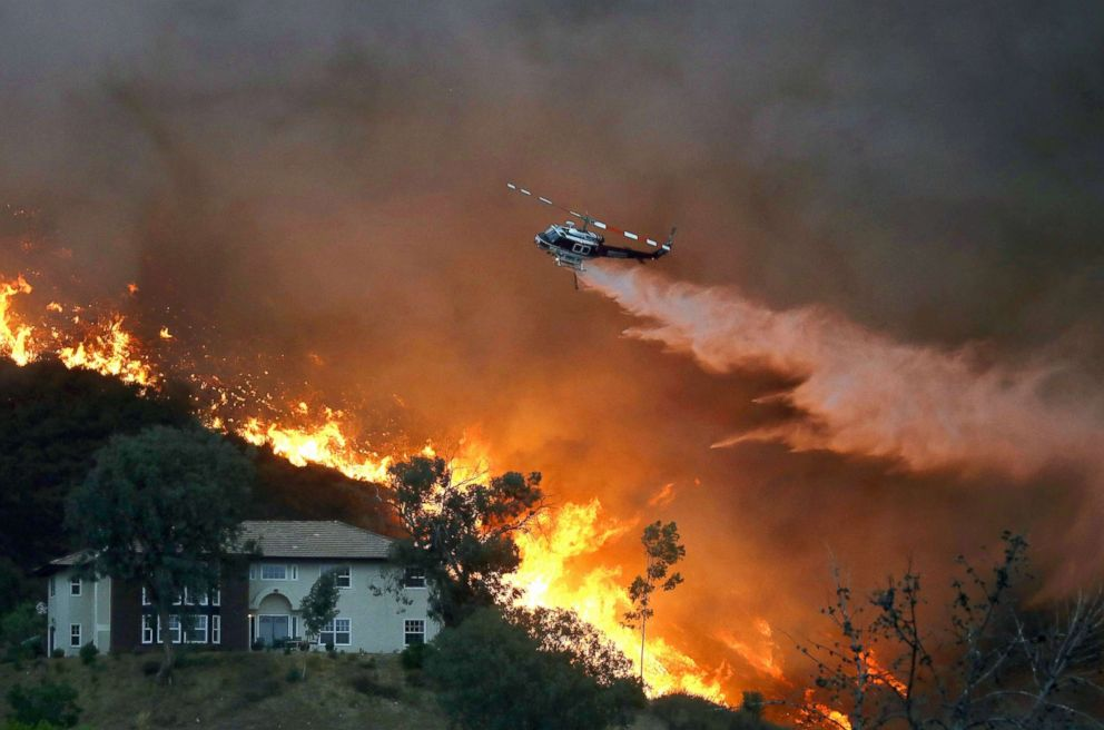 PHOTO: A firefighting helicopter makes a water drop as the Holy Fire burns near homes, Aug. 9, 2018, in Lake Elsinore, Calif.
