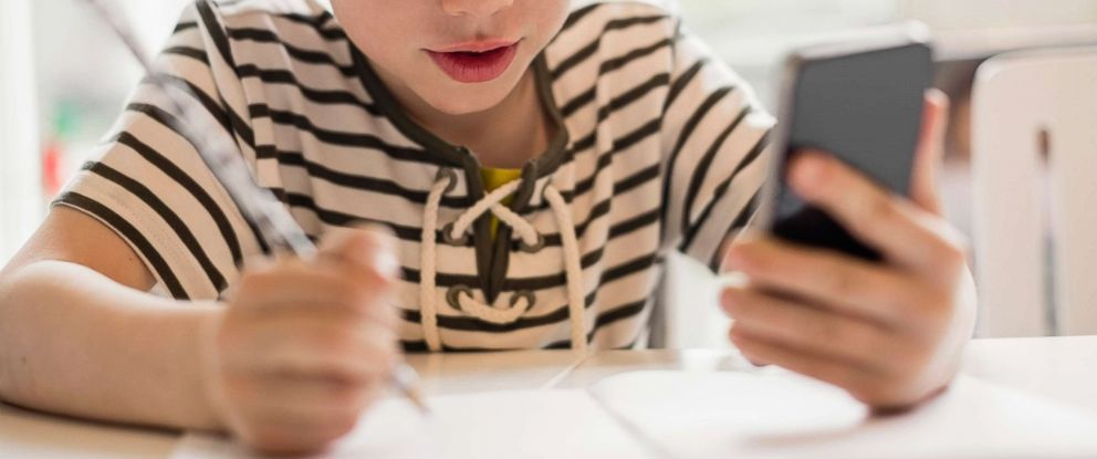 PHOTO: A stock photo depicts a young boy using a phone while doing his homework.