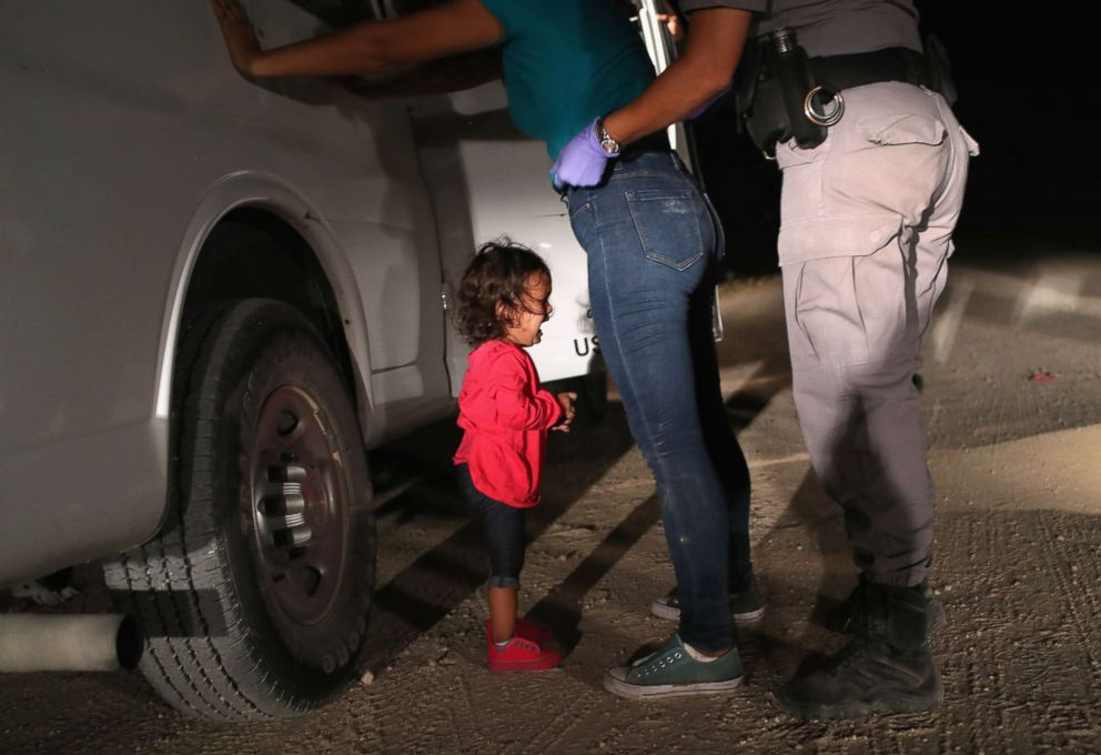 PHOTO: A two-year-old Honduran girl cries as her mother is searched and detained near the U.S.-Mexico border on June 12, 2018, in McAllen, Texas.