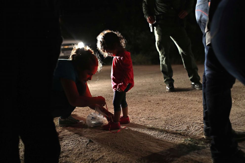 PHOTO: A Honduran mother removes her two-year-old daughters shoe laces, as required by U.S. Border Patrol agents, after being detained near the U.S.-Mexico border on June 12, 2018, in McAllen, Texas.