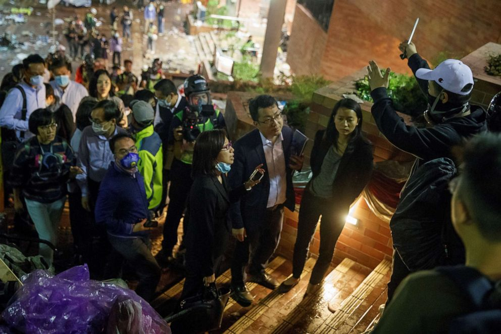 PHOTO: Teachers and relatives negotiate with protesters about the surrender of younger students from the occupied campus of the Hong Kong Polytechnic University that is surrounded by police in Hong Kong, Nov. 19, 2019.