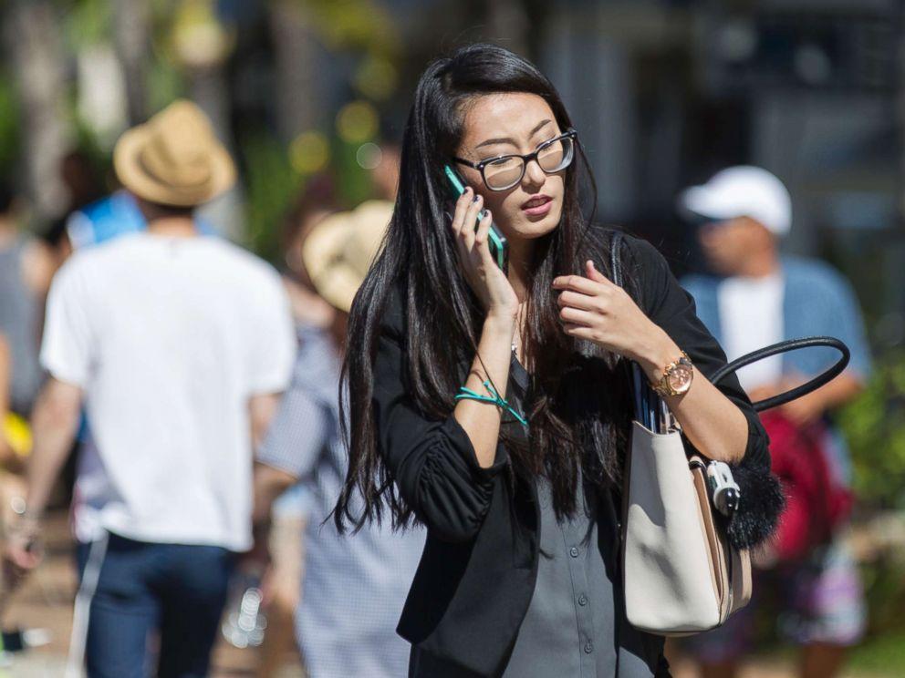 PHOTO: A pedestrian crosses Kalakaua Avenue talking on her cell phone, Oct. 24, 2017 in Honolulu.