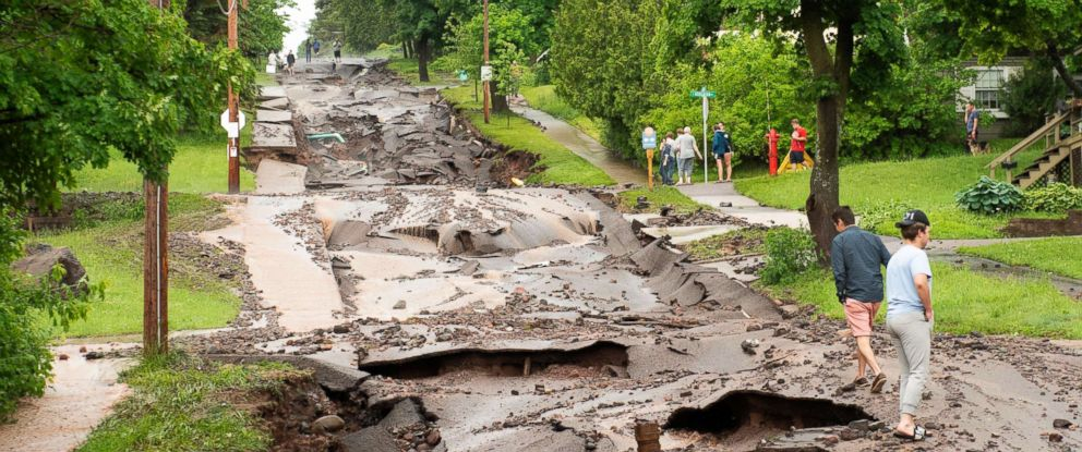 PHOTO: Residents look over the damage to Agate Street after heavy rains washed out the road in Houghton, Mich., June 17, 2018.