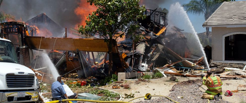 PHOTO: A firefighter and civilians train fire hoses on a burning home after an explosion and fire destroyed the home in Murrieta, Calif., sending up thick flames and closing several streets.