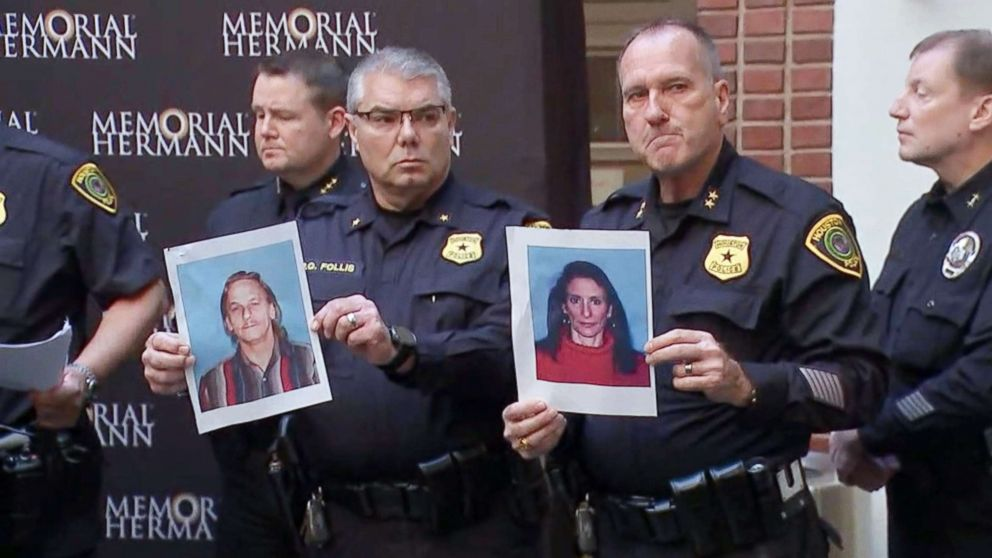 Houston police officers hold the photos of two suspects in the shooting of five police officers during a press conference at a hospital in Houston, Jan. 19, 2019. The suspects were identified as Dennis Tuttle, 59, and Rhogena Nicholas, 58.