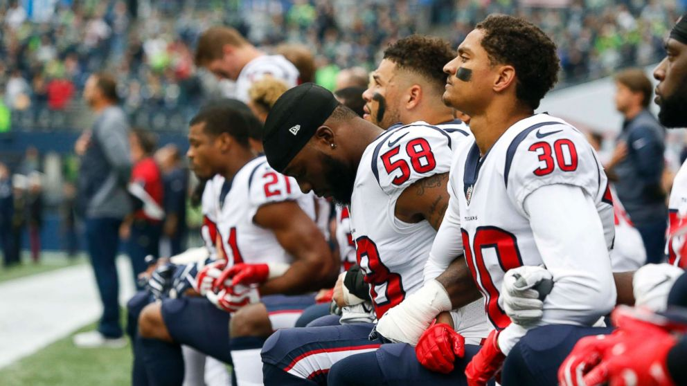 Houston Texans linebacker Lamarr Houston and cornerback Kevin Johnson kneel during the national anthem before kickoff against the Seattle Seahawks at CenturyLink Field in Seattle, Oct. 29, 2017.