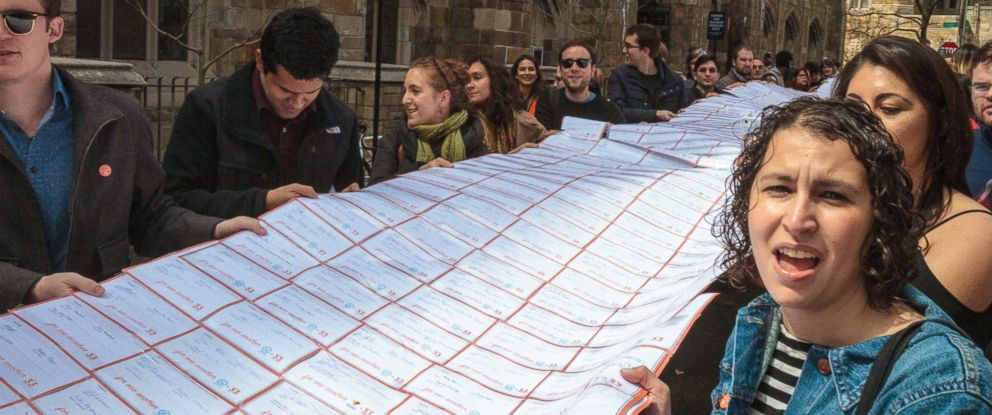 PHOTO: Protesters walk down College Street on Yale University campus in New Haven, Conn., holding signatures from a petition asking the school to engage in collective bargaining with the graduate student union, April, 2017.