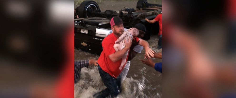 PHOTO: A still made from video shows good Samaritans rescuing an infant from an overturned vehicle caught in rushing water after storms struck in East Texas, April 29, 2017.