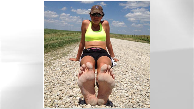 PHOTO: In this June 21, 2012 photo, Rae Heim takes a break from her cross-country barefoot run a few miles outside of Brooklyn, Iowa.