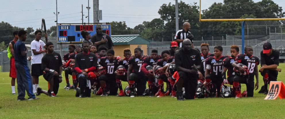 PHOTO: The Beaumont Bulls, a youth football team from Beaumont, Texas, kneel during the playing of the national anthem prior to a game on Saturday, Sept. 10, 2016.
