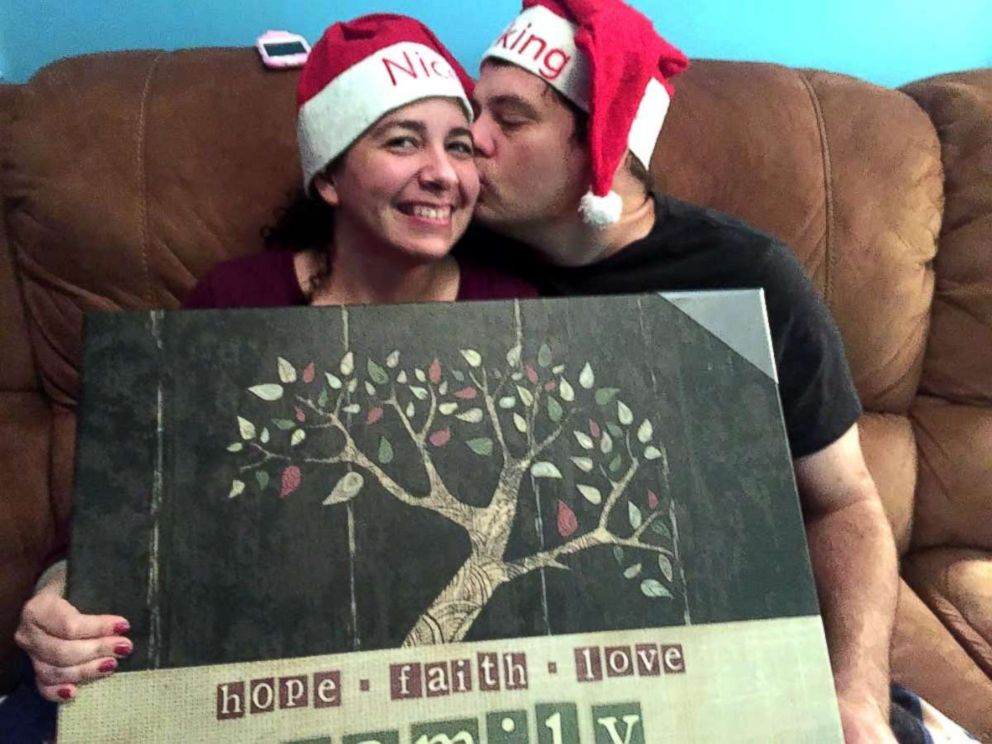 PHOTO: Hannah Overton and her husband hold up one of their Christmas presents.