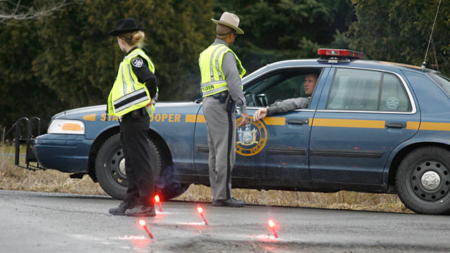 Photo: New York State Troopers and a Madison County Sheriffs deputy block off John Peet Road, outside Canastota, N.Y.