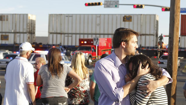 PHOTO: Bystanders react after a flatbed truck carrying wounded veterans and their families during a parade was struck by a train Thursday on Garfield in Midland.