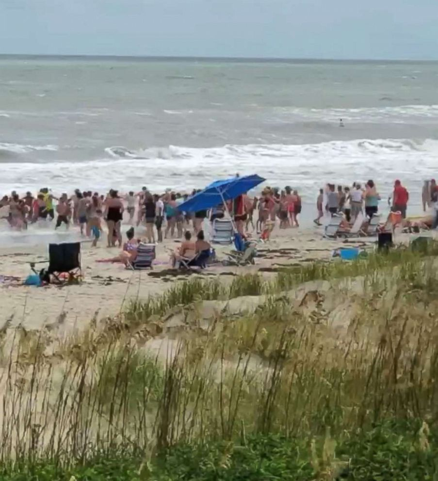 PHOTO: Beach-goers in Emerald Isle, North Carolina, formed a human chain to help get swimmers out of the rough surf.