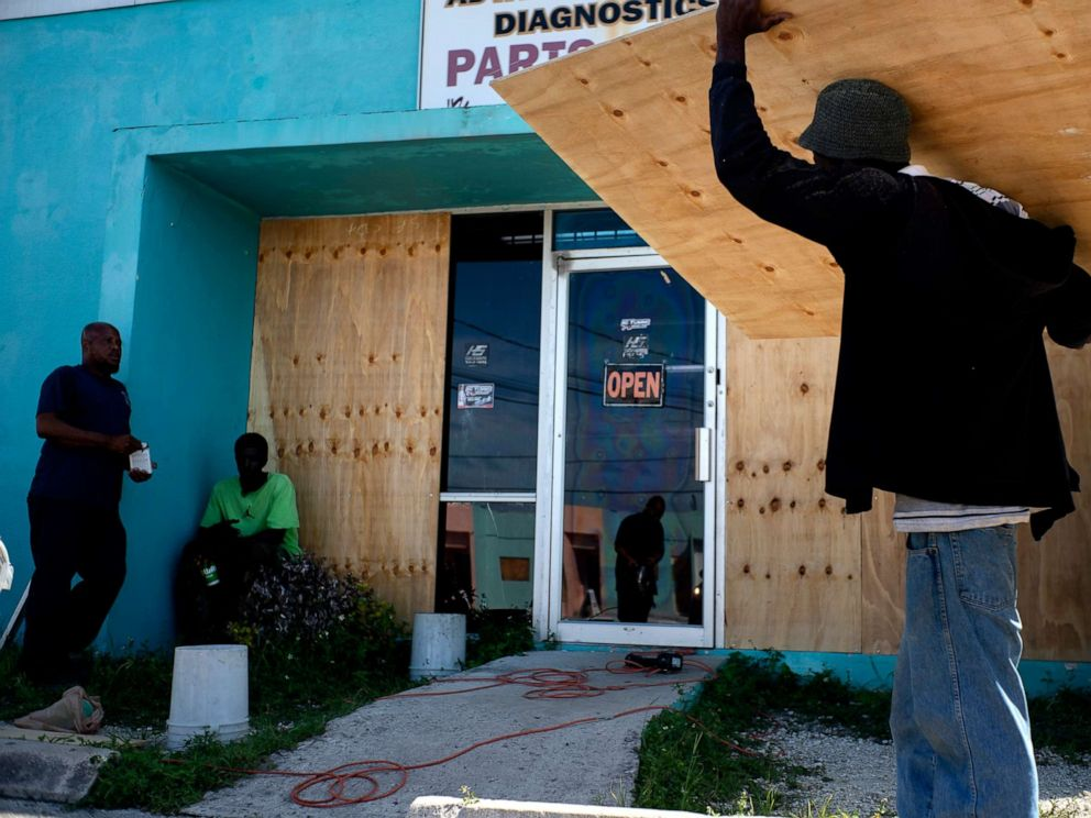 PHOTO: Workers board up a shop window front as they make preparations for the arrival of Hurricane Dorian, in Freeport, Bahamas, Friday, Aug. 30, 2019.