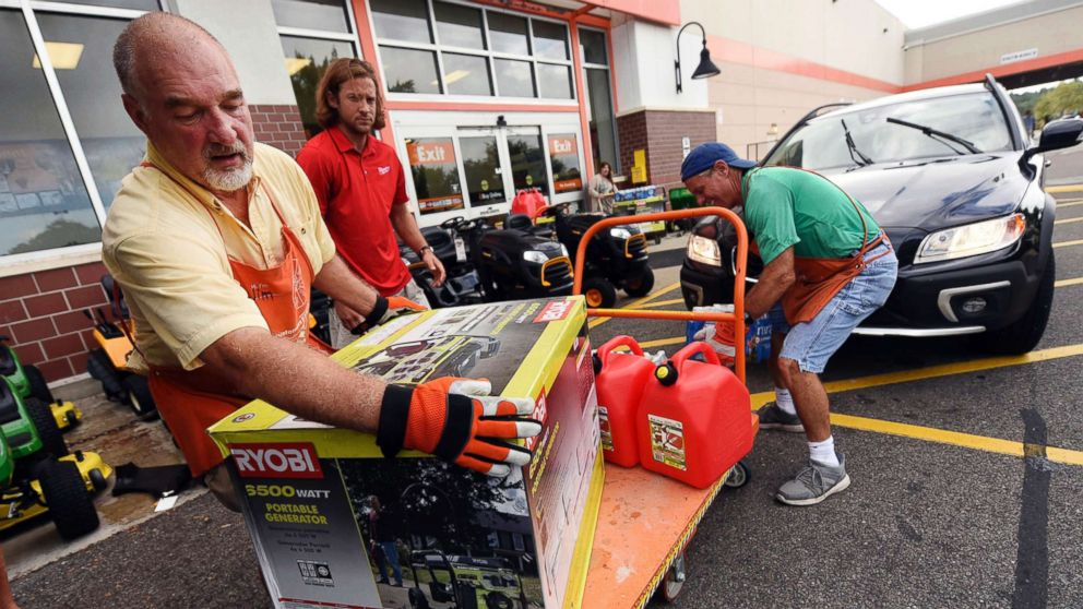 Jim Craig, David Burke and Chris Rayner load generators as people buy supplies at The Home Depot on Monday, Sept. 10, 2018, in Wilmington, N.C.