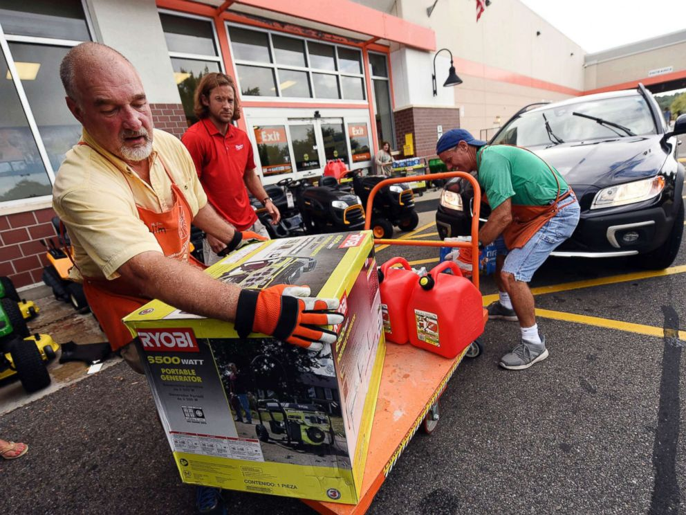 PHOTO: Jim Craig, David Burke and Chris Rayner load generators as people buy supplies at The Home Depot on Monday, Sept. 10, 2018, in Wilmington, N.C.