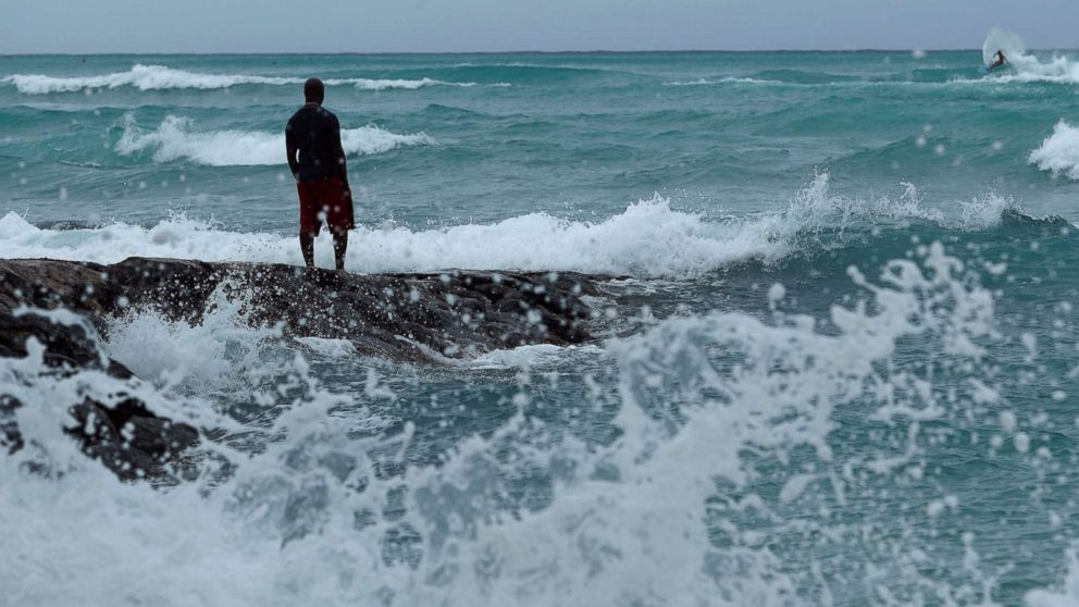 A man stands along the beach as waves crash on shore due to Hurricane Lane, Aug. 23, 2018, in Honolulu, Hawaii.