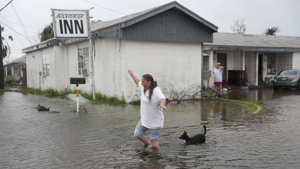 Valerie Brown walks through a flooded area after leaving the apartment that she road out Hurricane Harvey in, Aug. 26, 2017, in Rockport, Texas.