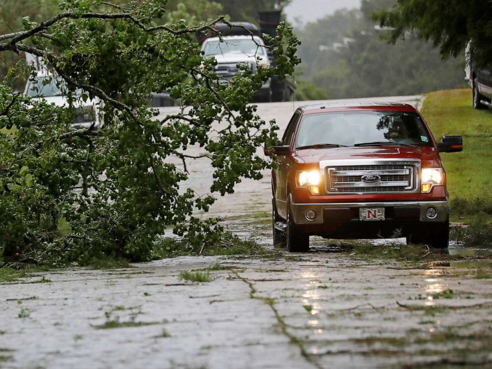 PHOTO:A truck maneuvers around a downed tree after strong wind gusts dropped it in west Morgan City, La., July 13, 2019.
