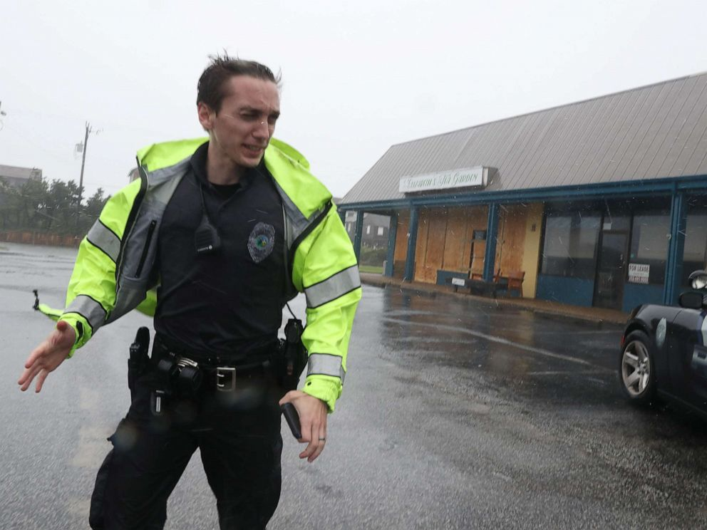 PHOTO: A police officer inspects a shopping center for damage after Hurricane Dorian hit the area, on Sept. 6, 2019 in Nags Head, N.C.