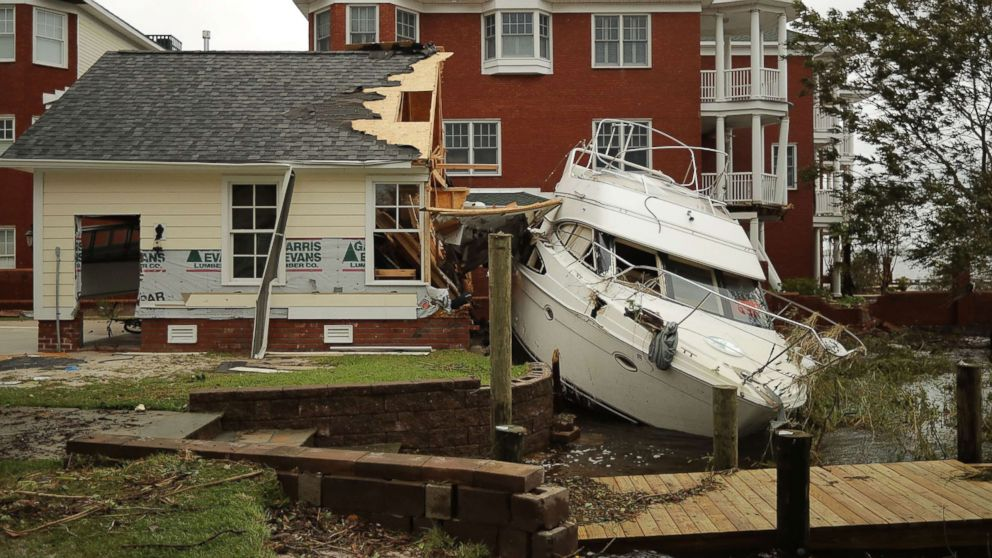 A boat lays smashed against a car garage, deposited there by the high winds and storm surge from Hurricane Florence along the Neuse River, Sept. 15, 2018, in New Bern, N.C.