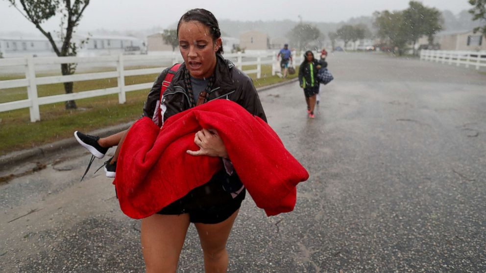 During a driving rain, Maggie Belgie of The Cajun Navy carries a child evacuating a flooding trailer community during Hurricane Florence in Lumberton, N.C., Sept. 15, 2018.