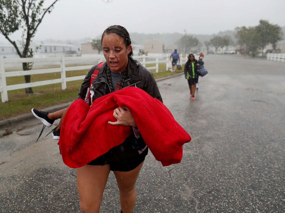 PHOTO: During a driving rain, Maggie Belgie of The Cajun Navy carries a child evacuating a flooding trailer community during Hurricane Florence in Lumberton, N.C., Sept. 15, 2018.