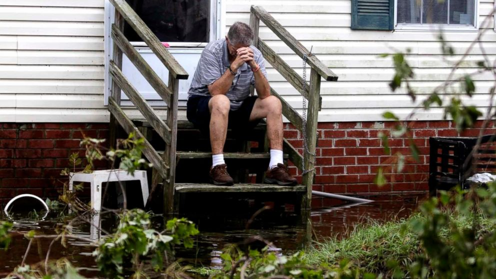 Joe Wiggins prays on the porch of his home surrounded by water after Hurricane Florence hit Emerald Isle N.C., Sept. 16, 2018.