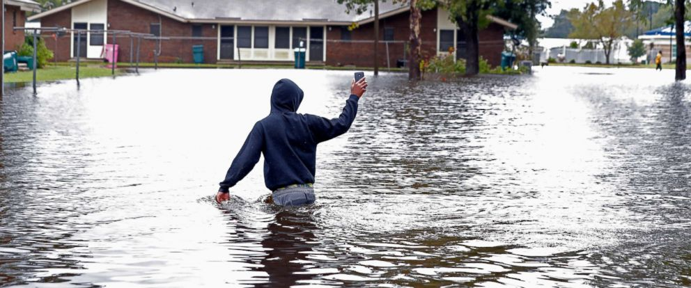 PHOTO: Camrey Mosley walks down a street through floodwaters from Hurricane Florence, in Marion, S.C., Sept. 16, 2018.