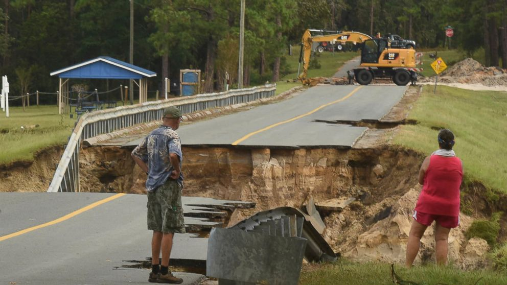 Mary and Phil Pongonis look at the damaged roadway from Hurricane Florence in Boiling Spring Lakes, N.C., Sept. 18, 2018.