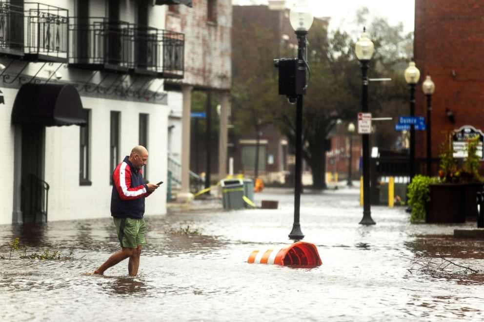 PHOTO: People walk through flooded Water Street as Hurricane Florence comes ashore in Wilmington, N.C., Sept. 14, 2018.