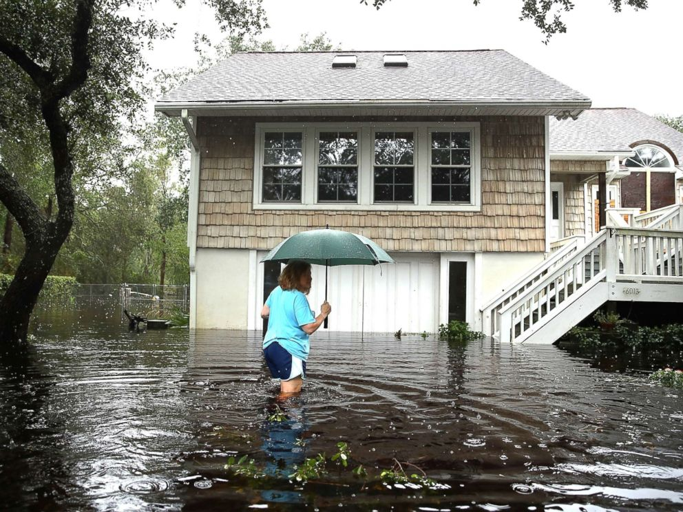 PHOTO: A woman makes her way to her home that is surrounded by flood waters after Hurricane Florence passed through the area on Sept. 15, 2018, in Southport, N.C.