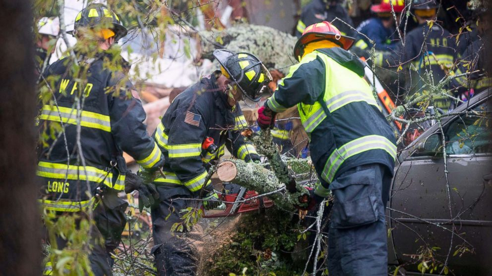 Rescue workers attempt to remove a giant tree that toppled onto a house when Hurricane Florence came ashore in Wilmington, N.C., Sept. 14, 2018.A mother and infant were killed in the incident and the father was transported with injuries.