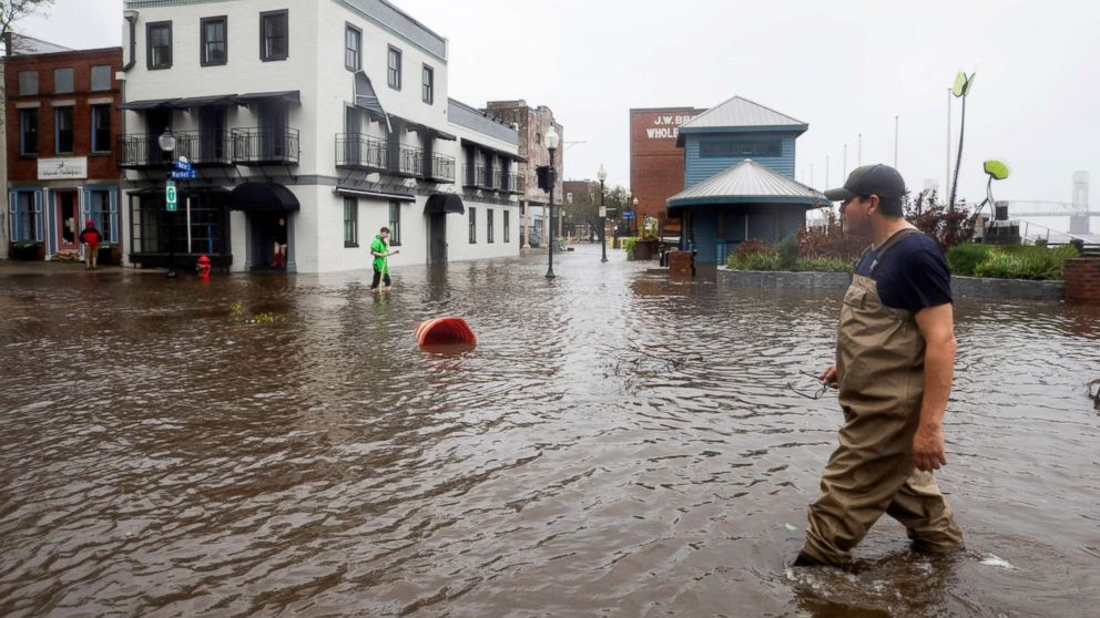 People walk through flooded Water Street as Hurricane Florence comes ashore in Wilmington, N.C., Sept. 14, 2018.